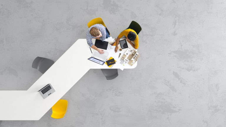 overhead of two employees working on their laptops