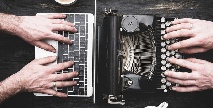 Laptop and typewriter both working with coffee
